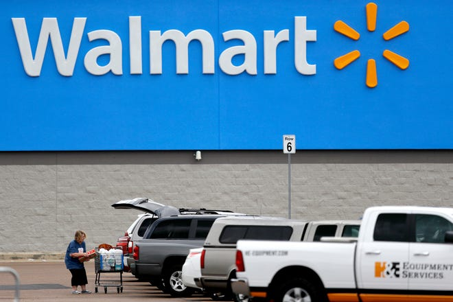 """A woman pulls groceries from a cart to her vehicle outside of a Walmart store in Pearl, Miss., in March. Walmart has reversed course, announcing Friday it is returning ammunition and firearms to their displays in its U.S. stores. The nation's largest retailer had previously said it had removed the items from displays due to """"civil unrest"""" in some areas of the country but said Friday the items had been restored to displays because the unrest has remained isolated."""