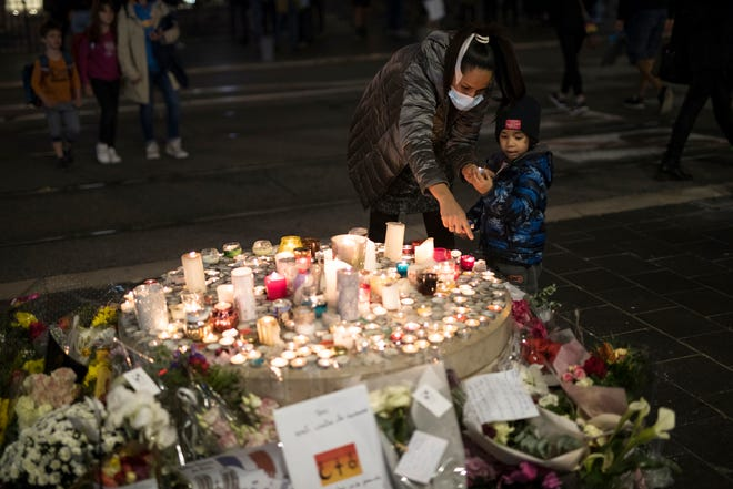 A family lights a candle in front of the Notre Dame church in Nice, France, on Friday. A new suspect is in custody in the investigation into a gruesome attack by a Tunisian man who killed three people in a French church. France heightened its security alert amid religious and geopolitical tensions around cartoons mocking the Muslim prophet.