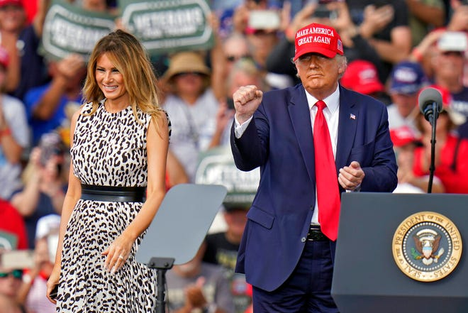 President Donald Trump pumps his fist as first lady Melania Trump smiles at supporters after a campaign rally Thursday, Oct. 29, 2020, in Tampa.