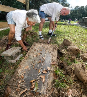 Carol Kern and her husband, Ernie, work on raising and saving a Vietnam veteran's headstone, which had sunken into the ground at the new Belleview Cemetery.