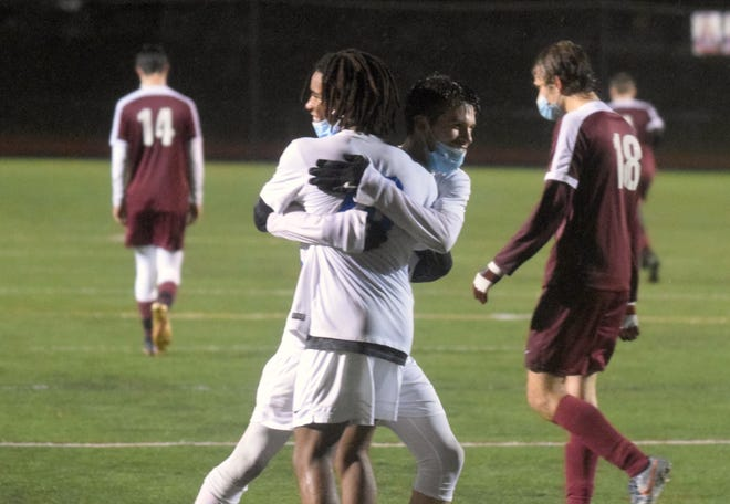 Winnacunnet High School senior Christopher Lepere, facing right, reacts with teammate Jude Smith following their 2-0 win over Portsmouth on Thursday night. To the right is the Clippers' Keghan Myers (18).