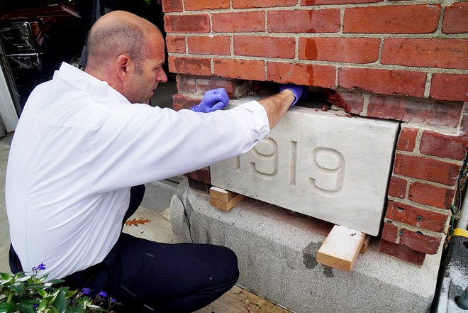 Fire Chief Todd Germain, opens the 1919 cornerstone time capsule Friday, at the Court Street firehouse in Portsmouth.
