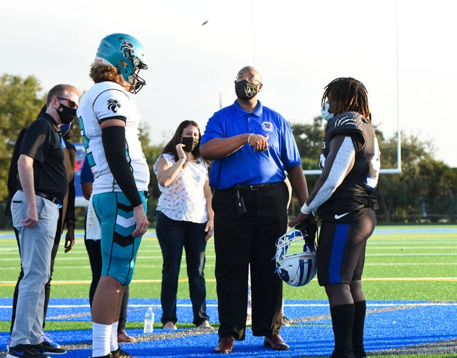 Palm Beach County School Superintendent Donald Fennoy, center, does the ceremonial coin toss as Royal Palm Beach quarterback Peyton Mainolfi, left and Wellington defensive tackle Denali Smith, right, look on before the start of the game between Wellington and Royal Palm Beach last October.