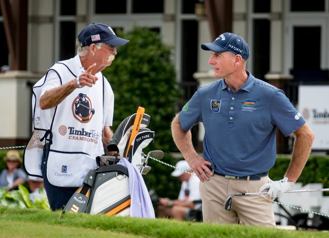 Jim Furyk listens to his caddy, Mike 'Fluff' Cowan, before hitting from the bunker during the first round of the TimberTech Championship Friday in Boca Raton.
