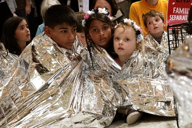 WASHINGTON, DC - JUNE 21:  Children wrap themselves up with Mylar blankets to 'symbolically represent the thousands of children separated from families on the border, sleeping on floors and held in cages', during a protest at the rotunda of Russell Senate Office Building June 21, 2018 on Capitol Hill in Washington, DC. Activists staged a demonstration to protest the Trump Administration's policy to separate migrant families at the southern border.  [Photo by Alex Wong/Getty Images]
