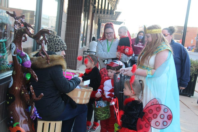 Cherie Welch hands out treats during the Spooktacular Downtown Trick-Or-Treat Walk on Friday, Oct. 30, 2020.