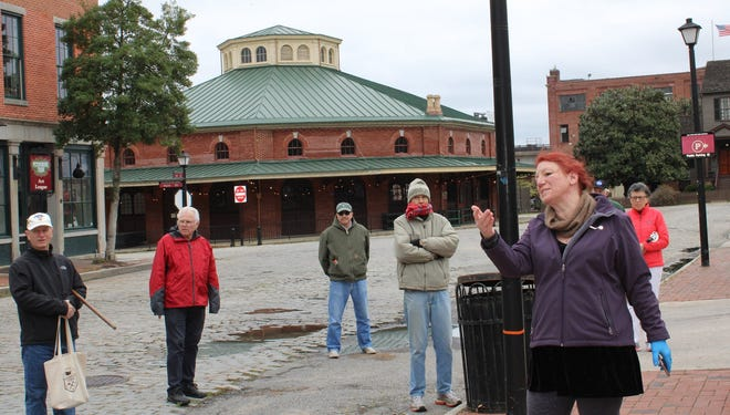 Michelle Murrills guides the Historic Petersburg Foundation's inaugural socially-distanced Petersburg Spring Walking Tour through Old Towne on March 21, 2020. The historic Farmers Market building is in the background.