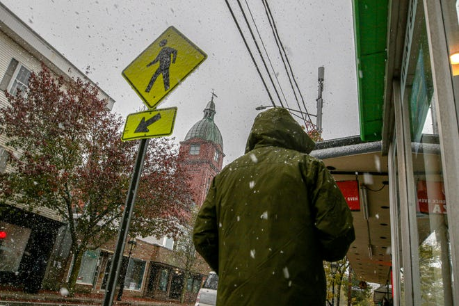 A walker passes through snow showers on Main Street in Warren as the first snow of the season hits Rhode Island.