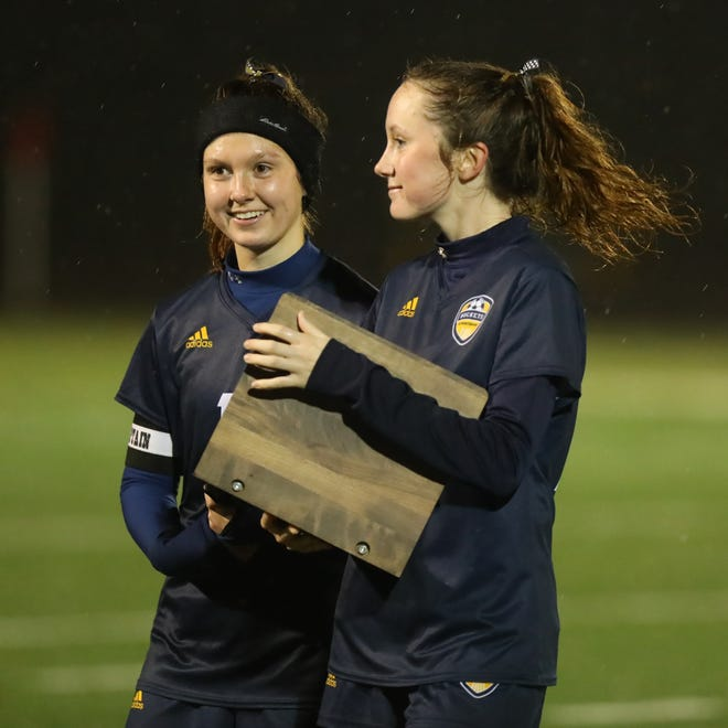 Streetsboro senior captains Abby Pincoe and Erika Richards are presented the district runner-up trophy after Thursday's game against West Geauga.