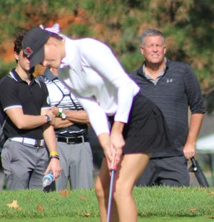 Maren Seaholts of Kent Roosevelt putts with her family looking on.