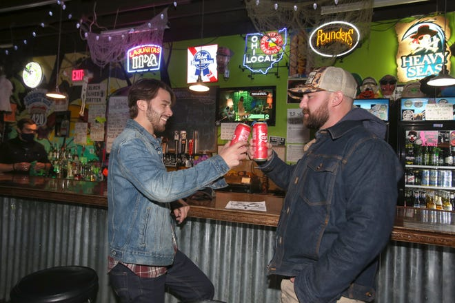Hunter Schwenk (left) and Paul Dickerson toast during 10 p.m. last call at Buzzbin in Canton on Oct. 28, 2020.