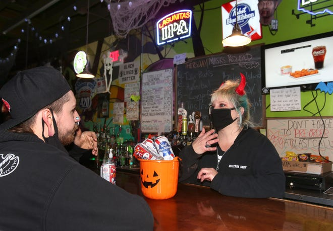 Bryce Blanton talks with Julia Bentley, co-owner of Buzzbin in downtown Canton, after ordering a bucket of Pabst Blue Ribbon during last call.