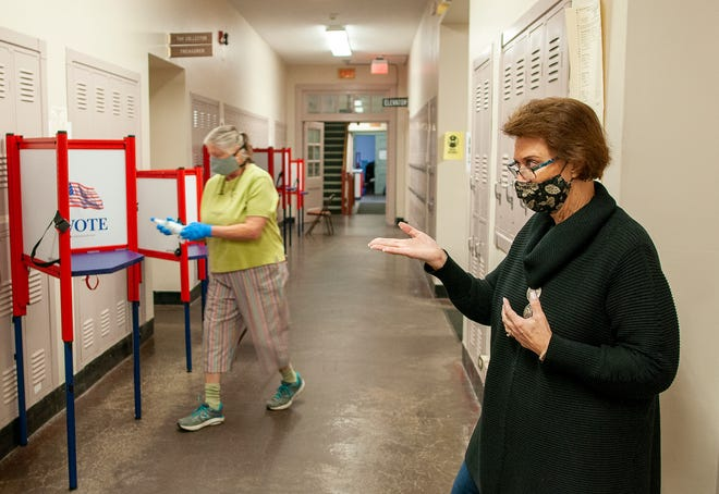 LEICESTER - Sharon Nist sanitizes voting booths after each voter and Leicester Town Clerk Deborah K. Davis describes the process for early voting in Town Hall on Oct. 29.