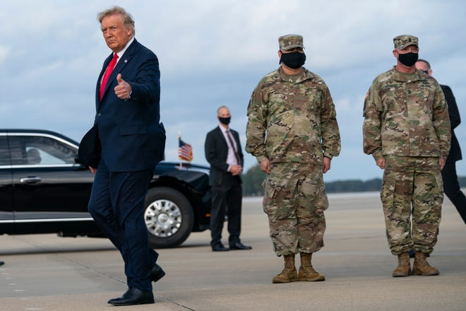 President Donald Trump gives a thumbs up after arriving at Pope Army Airfield for an event with troops at Fort Bragg on Thursday.