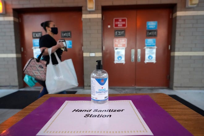 A hand sanitizing station is shown near an entrance to an elementary school in Broward County.
