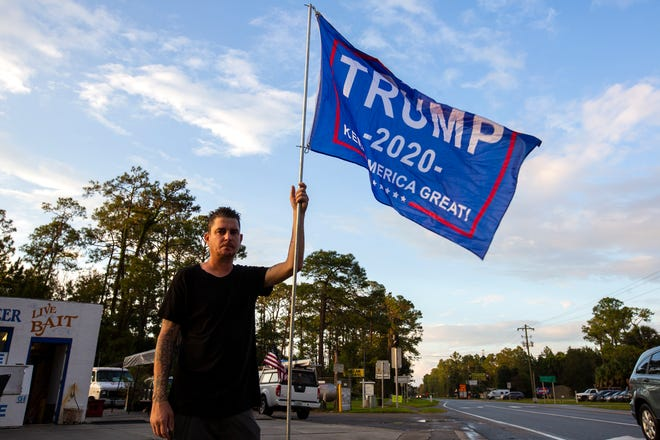 A supporter of President Trump waves a flag Thursday on the corner of State Road 26 and State Road 21 in Melrose.