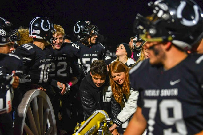 Members of the Pueblo South football team and students helps wheel the Cannon to the sideline after the Colts won the 2019 Cannon Game over Pueblo East on Oct. 11, 2020, at Dutch Clark Stadium.