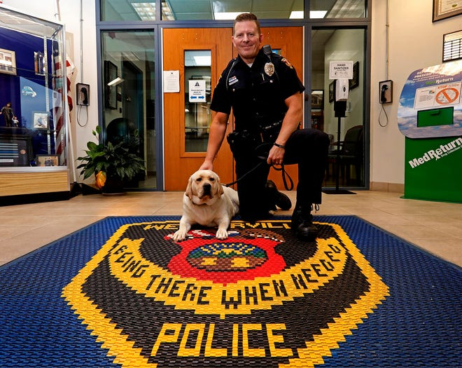 Westerville Division of Police officer Mark Wojciehowski kneels next to Chloe, the division's new therapy dog, Oct. 30. Chloe, a yellow English Labrador retriever, is the first therapy dog to join the force. The division saw the value of a therapy dog after the shooting death of officers Eric Joering and Anthony Morelli in February 2018.