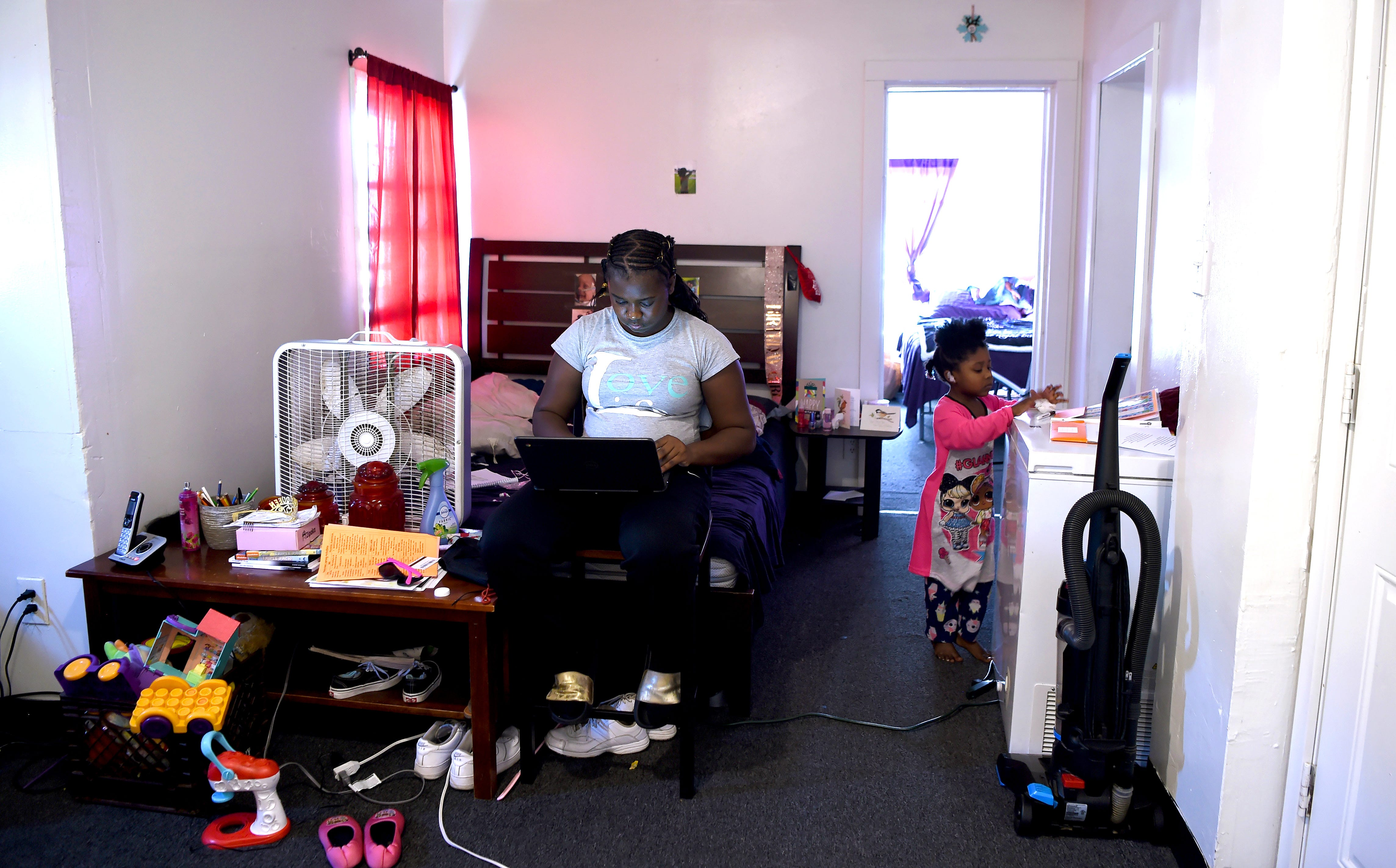 Raelin Powell attends her West Middle School classes remotely Oct. 15, 2020, in her family's apartment in Binghamton, N.Y. Her niece Phoenix Barnett, 3, is also enrolled in an online learning program.