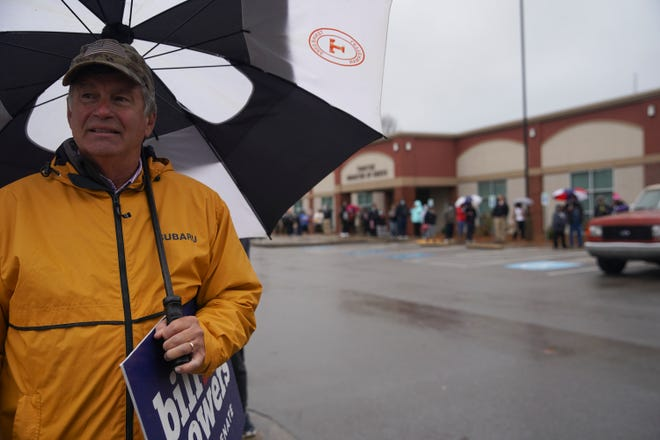 Bill Powers waves to cars passing by while campaigning on the last day of early voting at Veteran's Plaza in Clarksville, Tenn., on Thursday, Oct. 29, 2020.