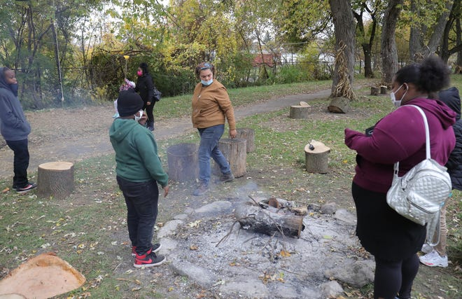 Leandra King owner of the Detroit Farm & Cider Mill opened for locals to enjoy hot cider, hayrides and a petting zoo keeps a fire pit going for people to stay warm on October 30, 2020.