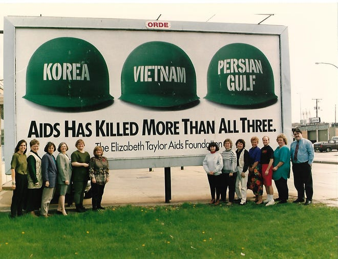 Staff of the CENTER Project, a Green Bay AIDS prevention, advocacy and support organization, in front of a billboard  in Green Bay in 1993.