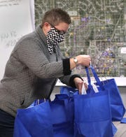 Lydia Armstrong, with Gluten Free Creations of Speedway, puts her home baked goods in bags to be delivered for the Fishers Farmers' Market, Friday, Oct. 30, 2020.  The fall market is virtual this year.  Customers order through the Fishers parks department website, online. The venders then drop off the orders, and parks staff separates the orders and delivers them to homes.