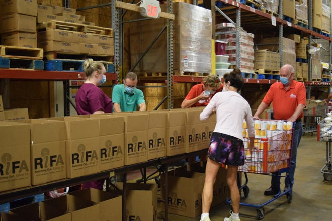 Volunteers put food into senior food boxes to send to senior citizens in need of food in RIFA's warehouse.