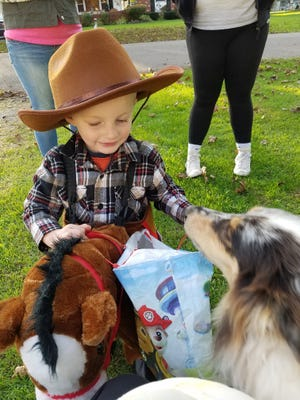 Annie Mae welcomes a miniature cowboy to Larry Fugate's house on Trick or Treat night.