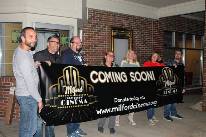 The nonprofit board hoping to reopen the Milford Cinema poses with a banner outside the closed theater at 945 E. Summit in Milford.
