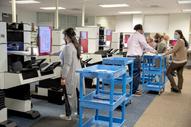 Election technician Claudia Hernandez, left, processes ballots as vote-counting gets underway in Riverside County for the Nov. 3 presidential general election inside the Riverside County Registrar of Voters building in Riverside, Calif., on October 29, 2020.
