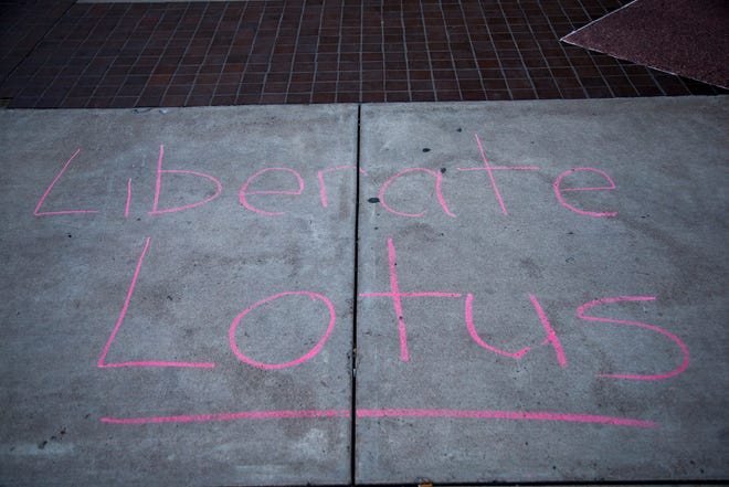 "Oct. 30, 2020; Phoenix, AZ, USA; A chalk message that says ""Liberate Lotus,"" at a press conference about Suvarna Ratnam, who was arrested in August while protesting police violence. Ratnam faces an aggravated assault with a deadly weapon charge. Credit: Meg Potter/The Arizona Republic"