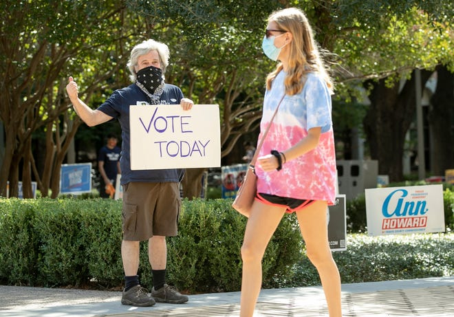 Kim Ludeke, left, encourages students to vote at an early voting location at the Gregory Gymnasium on the University of Texas campus, Tuesday, Oct. 13, 2020, in Austin, Texas. (Jay Janner/Austin American-Statesman via AP) ORG XMIT: TXAUS405