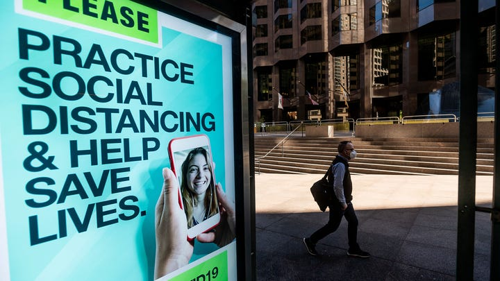 A man walks past a COVID-19 public service notice in San Francisco's financial district on Oct. 21, 2020.