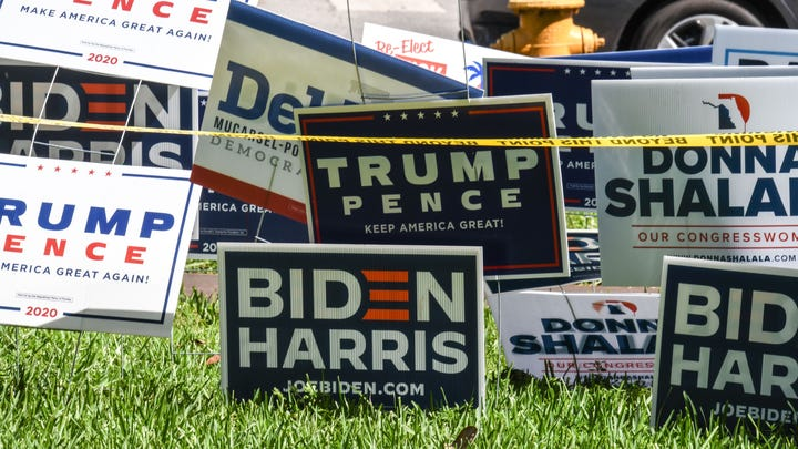 Trump-Pence and Biden-Harris signs are displayed outside The Coral Gables Branch Library in Miami, Florida, Oct. 27, 2020.