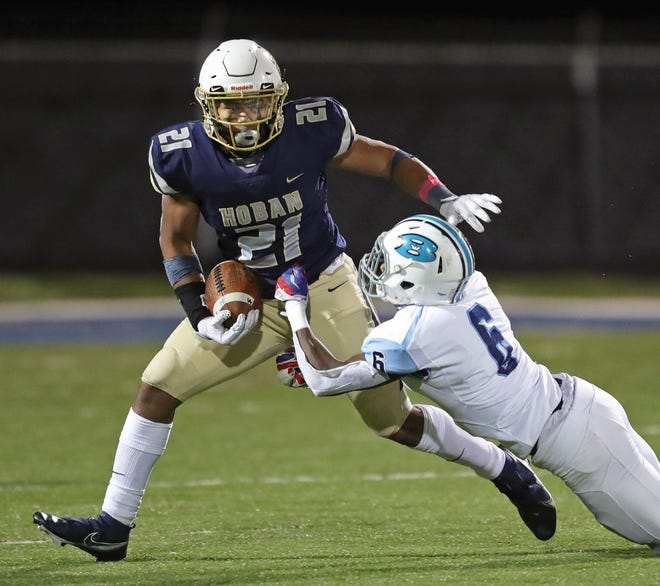 Hoban running back Victor Dawson is brought down by Benedictine linebacker Derell Bedingfield as he rushes for yards during the first half of Friday's game.