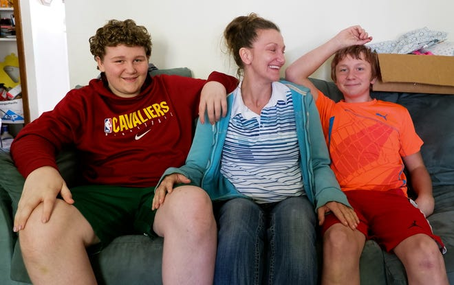 Served with an eviction notice at her Ellet apartment, Sarah Zader sits with her sons Kyle, left, and Anthony. The family doesn't know where they'll go.