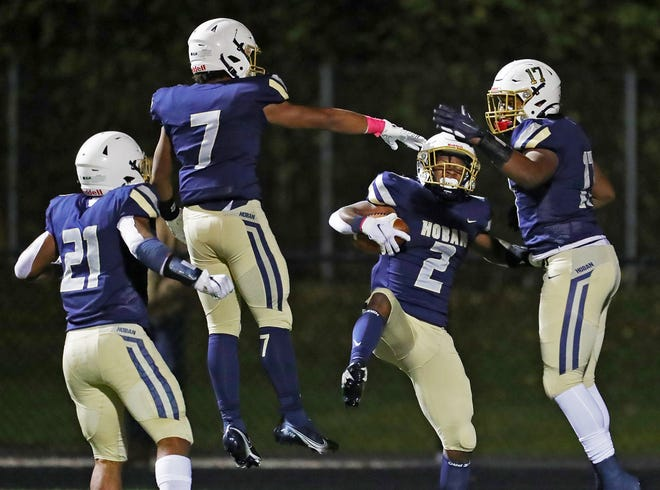 Hoban defensive back Kharion Davis, center, celebrates with teammates after an interception during the first half of a Division II regional semifinal football game against Benedictine, Friday, Oct. 30, 2020, in Akron, Ohio. [Jeff Lange/Beacon Journal]