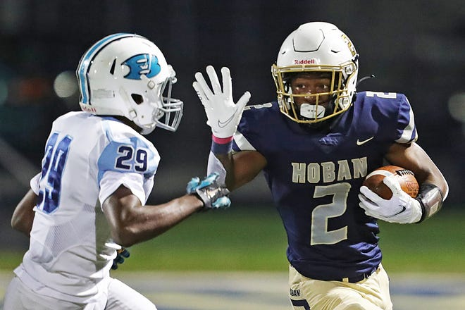 Hoban receiver Kharion Davis (2) stiff arms Benedictine defensive back Michael Hatcher during the first half of a Division II regional semifinal football game, Friday, Oct. 30, 2020, in Akron, Ohio. [Jeff Lange/Beacon Journal]