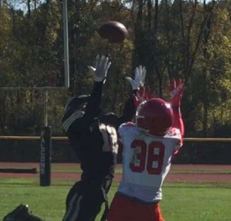 Burlington Township's Treyvon Reid (12) gets high in the air to break up a pass intended for Maurice Obanor of Rancocas Valley during their West Jersey Football League game Saturday.