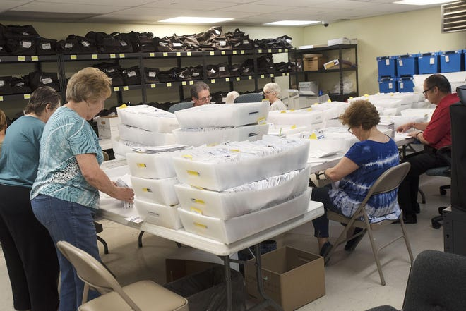 Election Bureau employees count some of the 18,603 primary election mail-in votes in June at the Beaver County Courthouse.