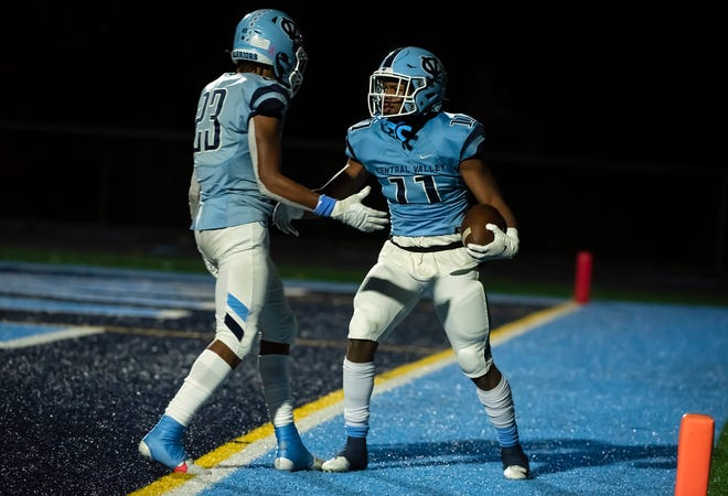 Central Valley's Landon Alexander (23) congratulates Amarian Saunders (11) after Sanders' touchdown run in the Warriors' quarterfinal playoff win over East Allegheny.
