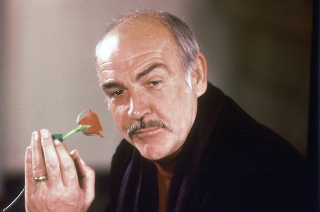"""In this Jan. 23, 1987 file photo, actor Sean Connery holds a rose in his hand as he talks about his new movie """"The Name of the Rose"""" at a news conference in London.  Scottish actor Sean Connery, considered by many to have been the best James Bond, has died aged 90, according to an announcement from his family. (AP Photo/Gerald Penny, File)"""