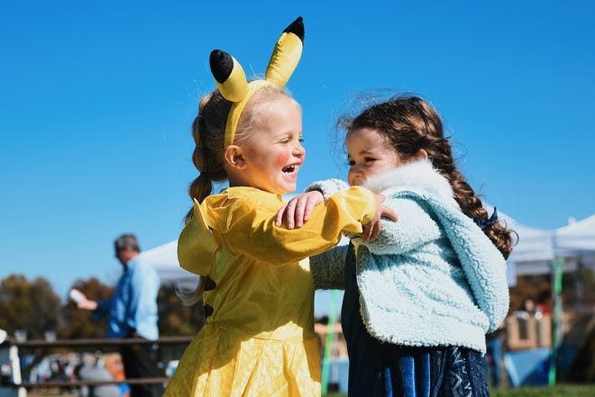 Dressed as Pikachu, Novalynn Price, 4, left, hugs her friend Vivian Seat, 4, who decided to dress as Elsa for Four Oaks Farm's Halloween celebration on Saturday.