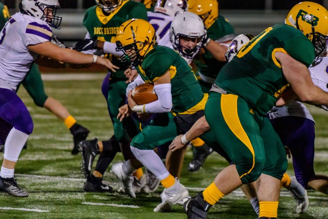 Rock Bridge quarterback Nathan Dent finds an opening to rush for a first down against Troy Buchanan on Friday night at Rock Bridge High School.