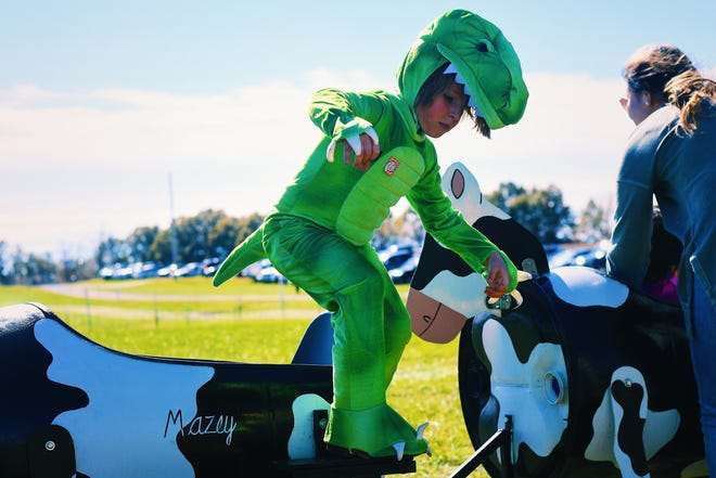 Dressed as a dinosaur, Von Connell, 4, hops out of a cow-shaped ride at Four Oaks Farm's Halloween celebration on Saturday.