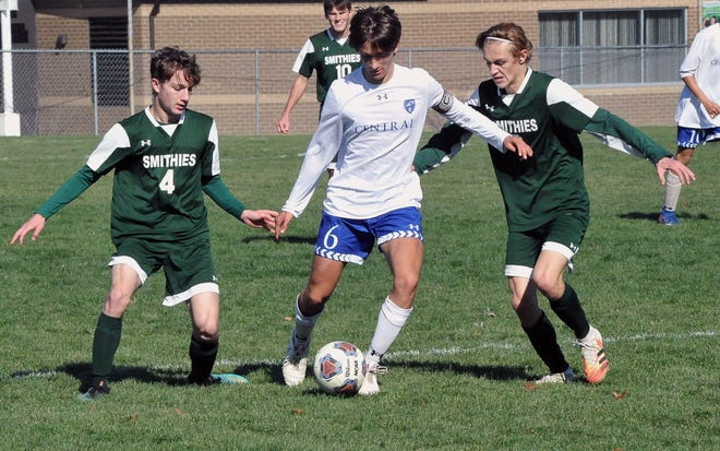 Central Christian's Kaden Schrock controls the ball in the midst of Smithville's Jacob Hanna and Caleb Hannah. Central won 1-0 for a seventh straight district title.