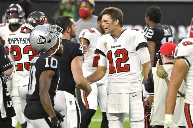 Tampa Bay Buccaneers quarterback Tom Brady (12) greets Las Vegas Raiders quarterback Derek Carr after an Oct. 25 game in Las Vegas.