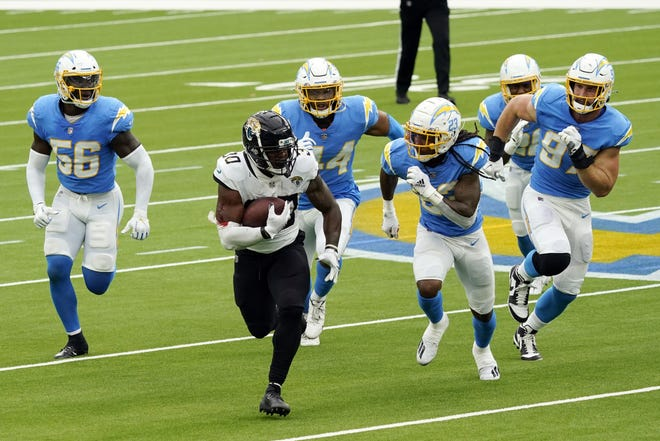 Jaguars rookie running back James Robinson, seen here running past Los Angeles Chargers defenders, has done his part to make his team competitive in 2020, but deficiencies in other areas have the Jaguars tied for last place in the AFC South.