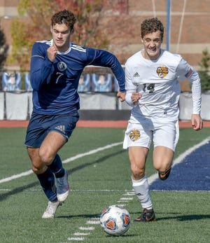 Hudson's Caleb Junko and Walsh Jesuit's Michael DelPrete chase the ball during the Explorers' 5-1 win in a Division I district final game Oct. 31 at Hudson Memorial Stadium. Junko and DelPrete each had a goal in the game.
